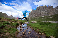 Young woman trail runner jumping over st