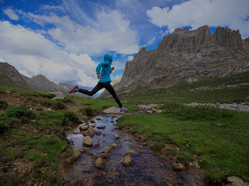 Young%20woman%20trail%20runner%20jumping%20over%20stream%20water%20at%20mountain_edited.jp