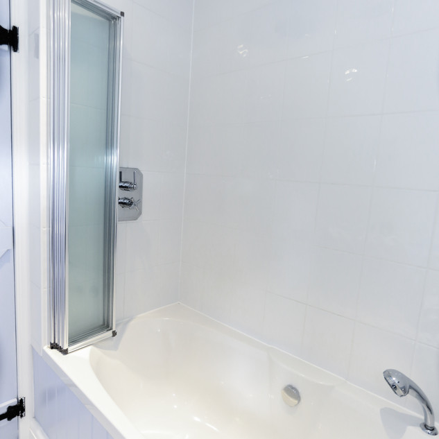 Private bathroom with bath and power shower above