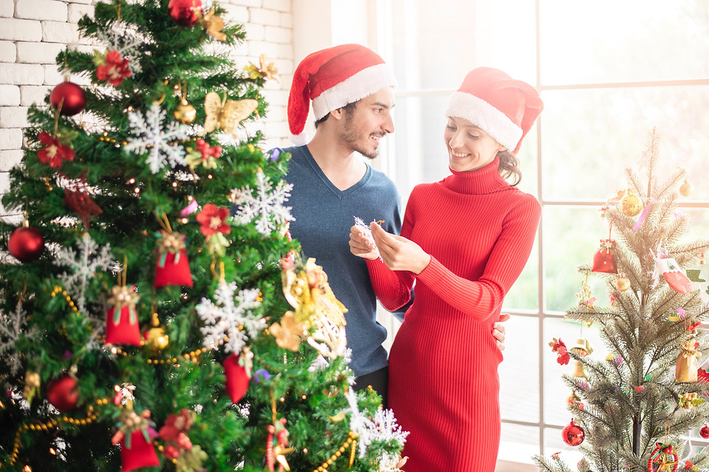 man and woman by christmas tree