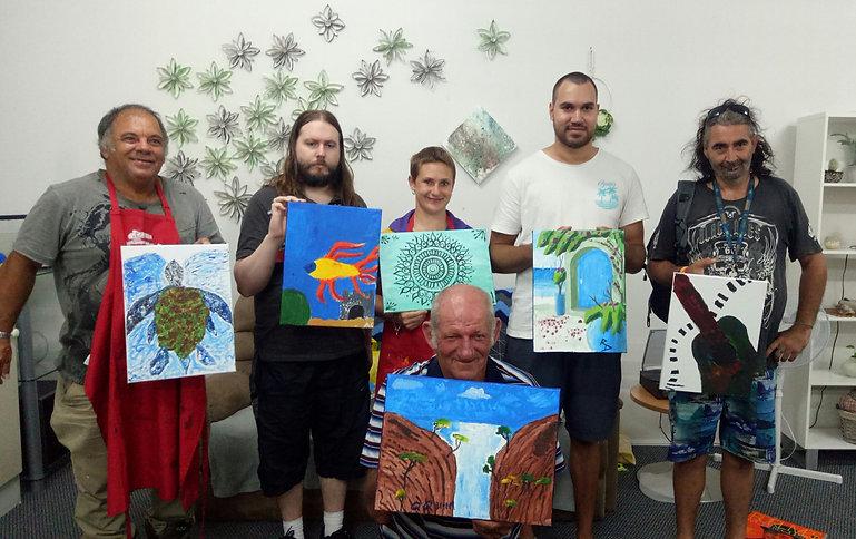 Progam participants holding paintings