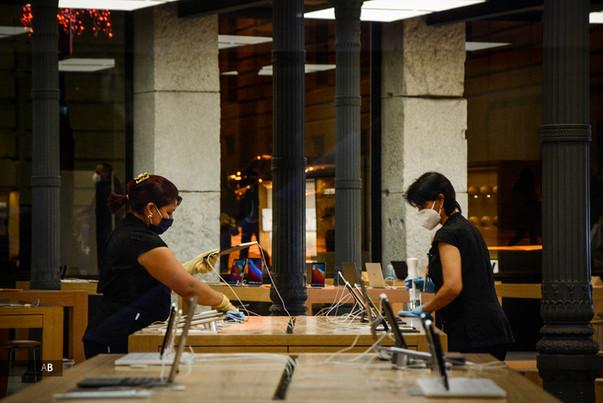 Dos trabajadoras de limpieza trabajan en la desinfección de la Apple Store en la Puerta del Sol por la crisis sanitaria de la Covid-19.