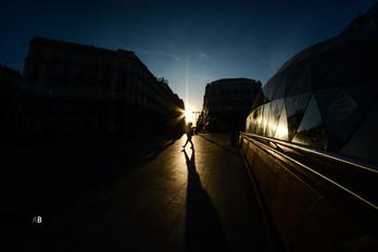 Un hombre camina por la Puerta del Sol