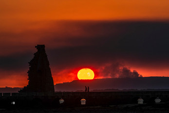 Vista de un incendio en A Pobra (A Coruña) y de la puesta de sol desde Cambados (Pontevedra)