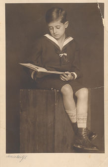 A damaged photo of a young boy reading