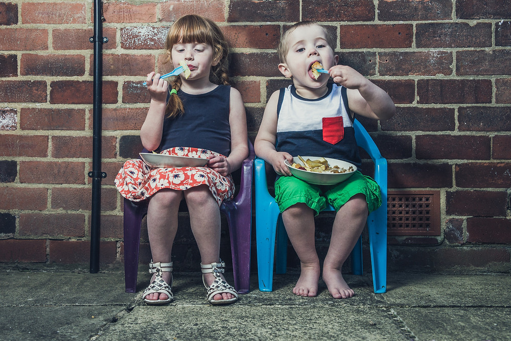 Kids eating fish and chips against a brick wall