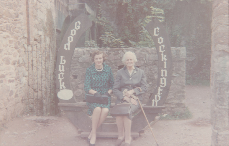 """Two Women sat on a bench that says """"Good Luck Cockington"""""""