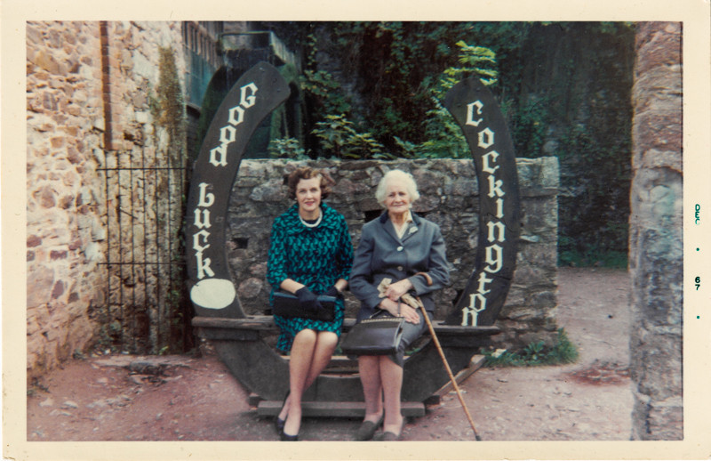 Two women sat on a bench in Cockington