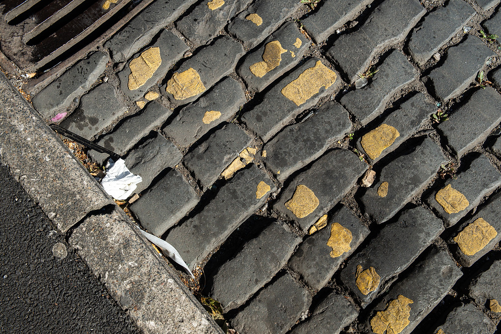 A cobbled Road with yellow lines