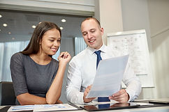 smiling businessman and businesswoman with papers meeting in office
