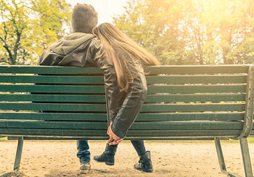 young couple sitting on a park bench