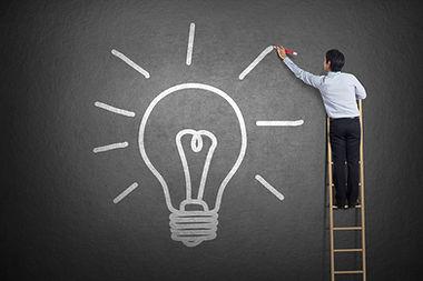 businessman standing on a ladder drawing light bulb