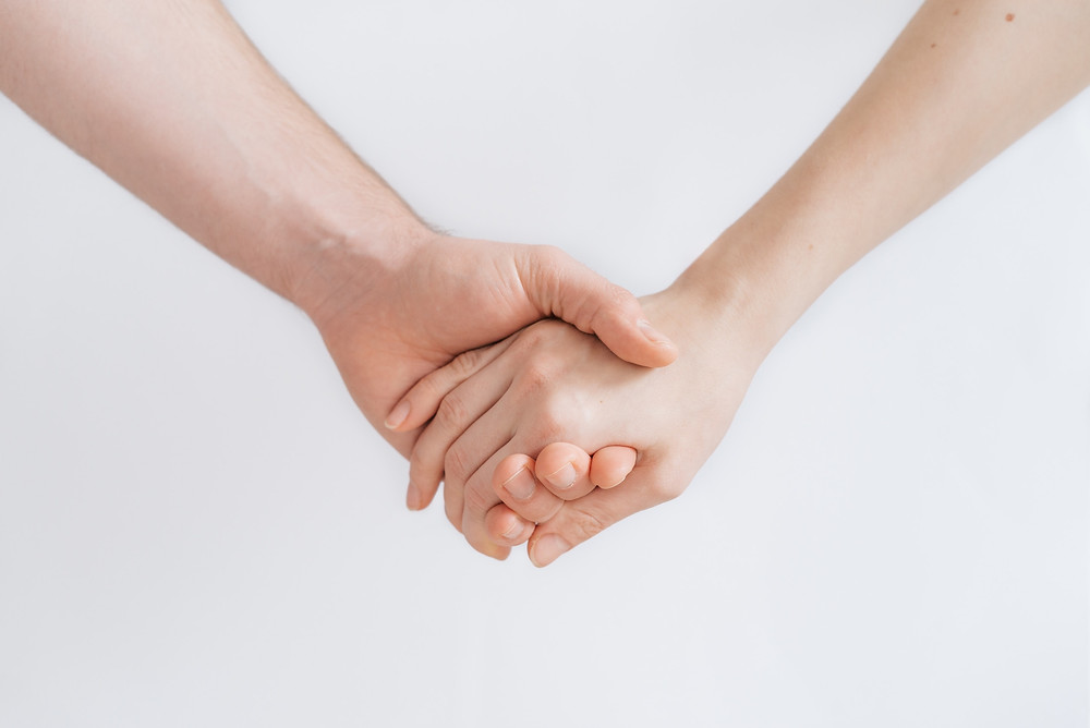 man and woman holding hands for moral support