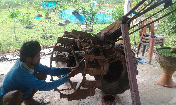 Fixing farm machinery in rural Thailand.