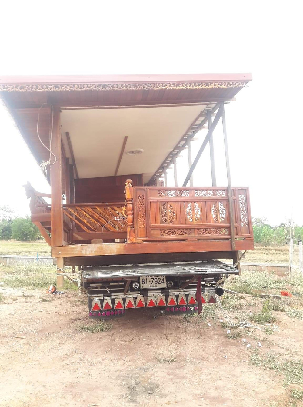 Traditional wooden thai house arriving on site on the back of a truck