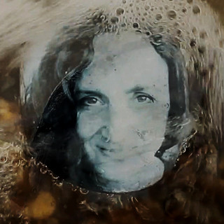 A still from the promotional video - I made a self portrait on a beach pebble then returned to the location I found it. ©Gillian Allard