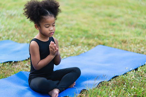 African american little girl sitting on the roll mat practicing meditate yoga in the park