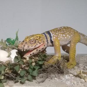 """31 - Thales Henrique Menezes Silva do Nascimento """"Pequeno assaltante de ninhos"""" (Escultura tradicional) Um pequeno Adamantinasuchus navae se aproveita do descuido de uma mãe para assaltar os ovos de um ninho."""
