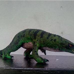 """04 - Áquila Guerlain Alves Dos Santos """"O Crocodilo Tinhoso de Gondwana - Gondwanasuchus Scabrosus"""" (Escultura em Biscuit) E uma escultura feita em biscuit, todas as escamas foram feitas a mão, a pintura foi baseada em crocodilos e alguns lagartos aquáticos, a escultura está na escala 1:5, ela tem 26cm de comprimento, demorou entre 26 a 28 dias, era para ela ter um cenario, mais não foi feito por falta de materiais."""