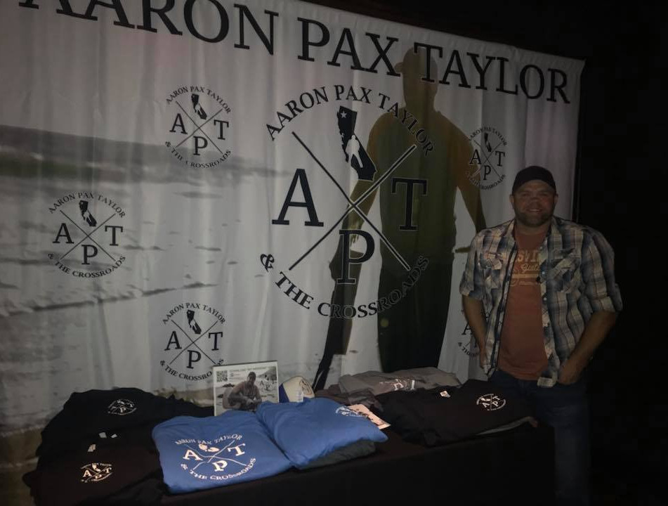 Aaron Pax Taylor with Merch table.jpg