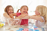 24508491-three-girls-making-cupcakes-in-