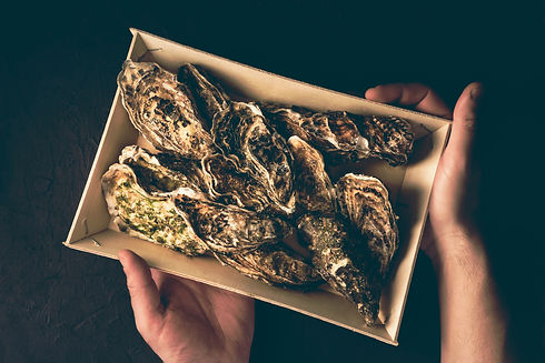 Fresh oysters in a wooden traditional box in male hands on a dark background. Fresh french