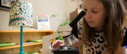 Girl looking through microscope