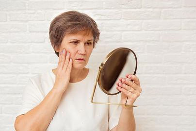 elderly-woman-looking-wrinkled-face-mirror.jpg