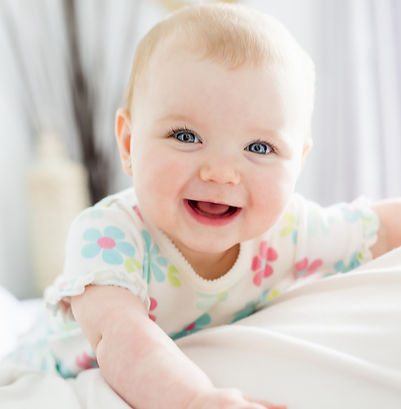 A Baby girl in white bedding at home loo