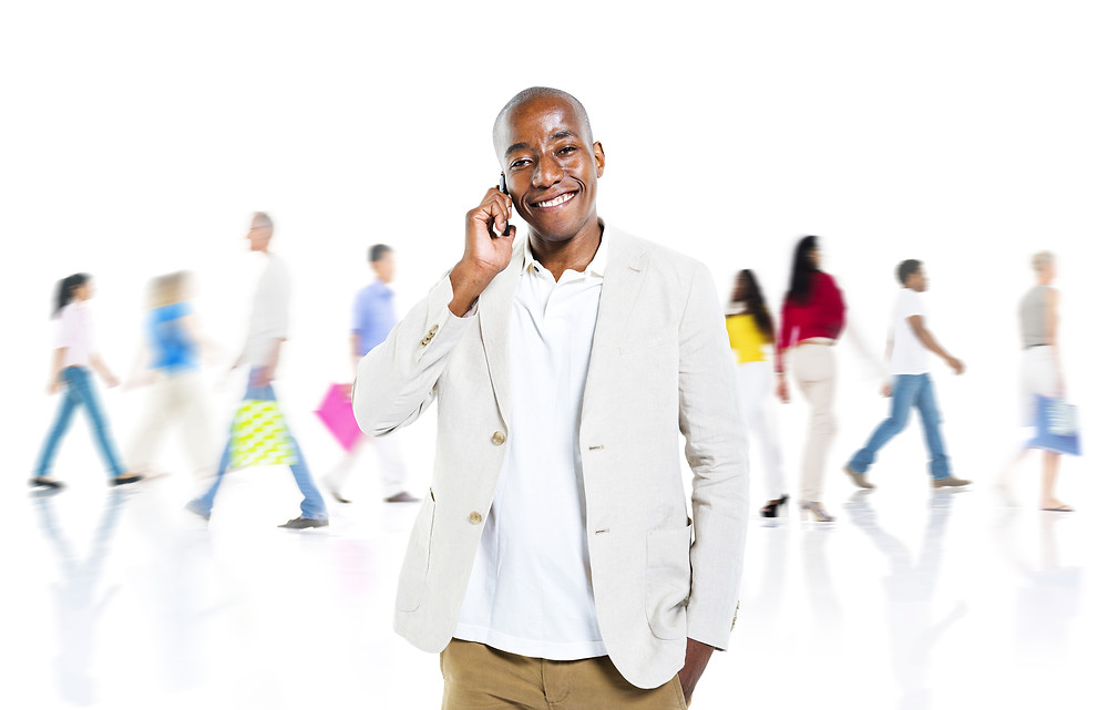 Cheerful African Man Talking On a Mobile Phone With Busy Background.jpg