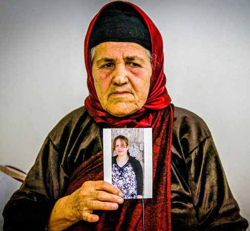 A Christian woman holds a photo of her daughter who was kidnapped by ISIS.  2015 Erbil, Iraq