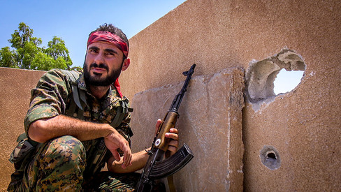 A member of the Syriac Military council prepares to return fire on ISIS members positioned 500 meters away.   2015 Hasakah, Syria