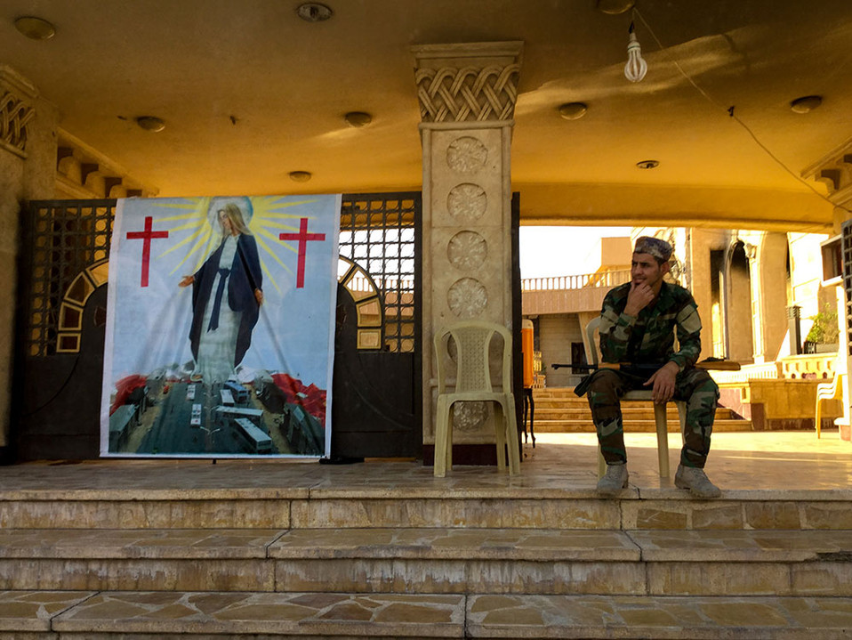A soldier guards the Church of the Immaculate Conception in Qaraqosh, Iraq. Qaraqosh is a few kilometers outside Mosul and is rebuilding after ISIS was driven out last in 2018.  2017 Qaraqosh, Iraq