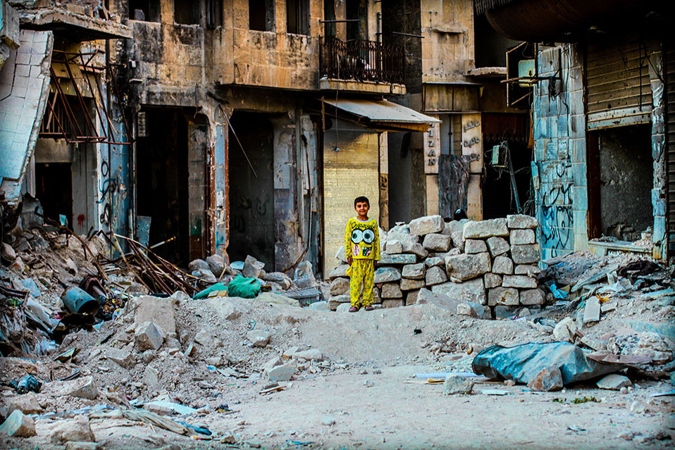 Ayoung boyposes for a quick photo on top of a pile of rubble just before sunset in West Aleppo, Syria.  2017 Aleppo, Syria