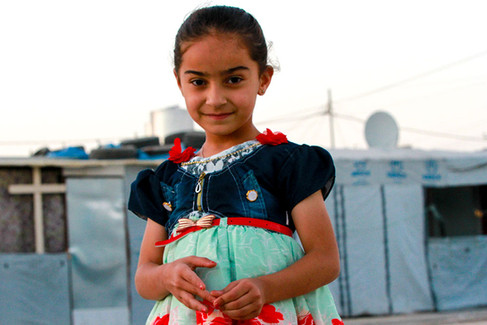 A young girl poses for a photo inside one of the Christian camps in Ankawa, Iraq.   2017 Erbil, Iraq