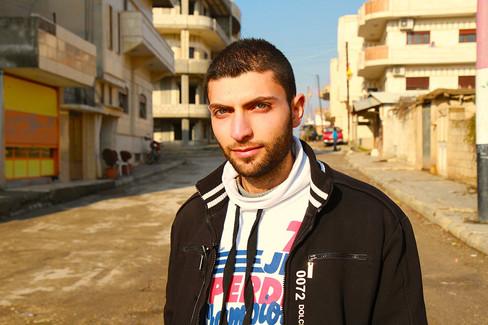 A young Syrian man walks the abandoned streets of Qamishli, Syria  2014 Al-Malakiah, Syria