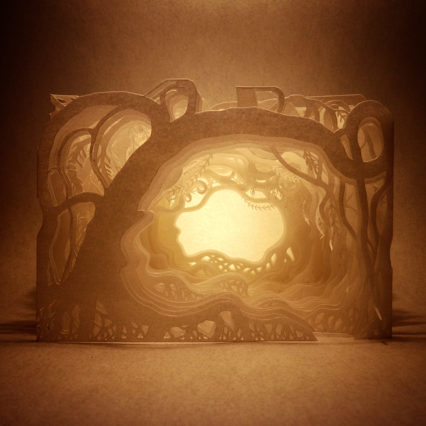 A photo of a paper creation by Ayumi Shibata - it's a 3D cut out of a path through a creepy wood with a light at the end of it. All the trees are curvy and spread out.