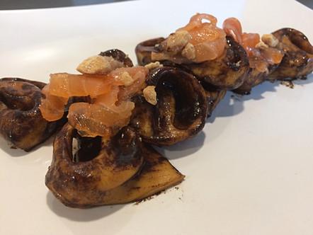 Tortelloni di zucca con crema all'aglio nero, salmone affumicato e frutta secca