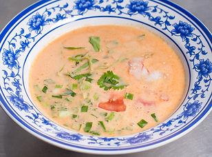 Немного острый суп на основе кокосового молока с креветками, пастой том ям, сливками, курицей, помидорами, кинзой, зелёным луком, помидорами, кукурузой и соком лайма