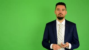 business-man-works-on-phone-green-screen