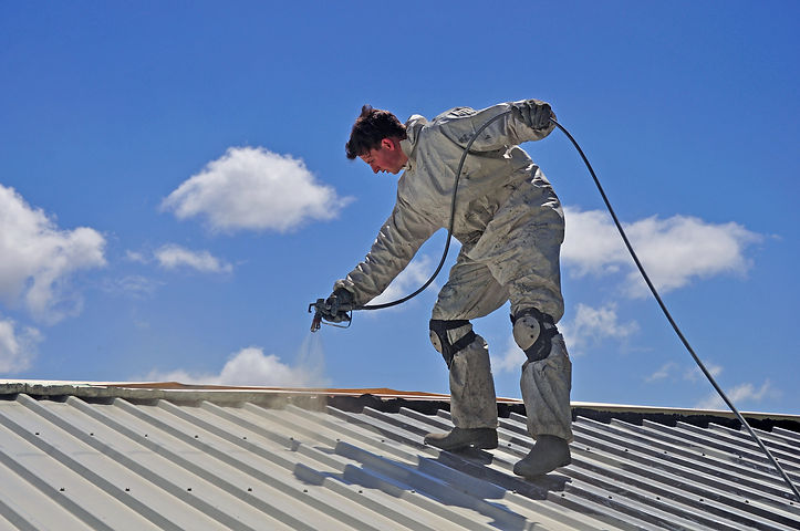 A tradesman uses an airless spray to paint the roof of a building