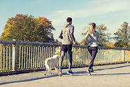 couple-with-dog-running-outdoors-P338CZ5