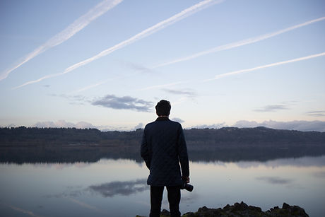 Man looking at a lake in a suit