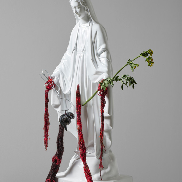 """Virgencita abortera. From the project """"Clandestinas"""". Fiberglass intervened with Paracas ringed knitting,  ceramic, wire, aluminum knitting sticks  and herb-of-grace. 2020. 71 x 28 x 18 cm."""