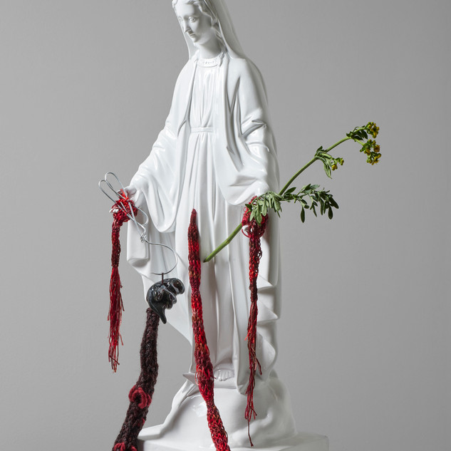 "Virgencita abortera. From the project ""Clandestinas"". Fiberglass intervened with Paracas ringed knitting,  ceramic, wire, aluminum knitting sticks  and herb-of-grace. 2020. 71 x 28 x 18 cm."