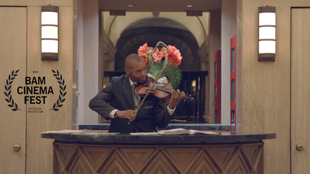 A New York City doorman wears many hats—father, art curator, and erstwhile violinist—as he works tirelessly to give back to his community in Haiti.