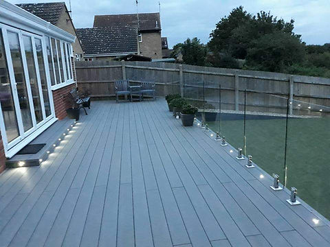 Modern decking with lighting and glass fencing around the edge