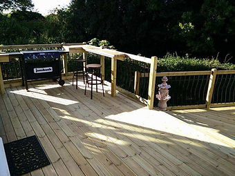 Traditional timber decking with fencing around the edge and BBQ