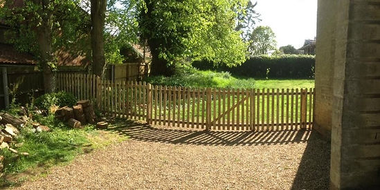 Timber picket fencing seperating garden and gravel driveway
