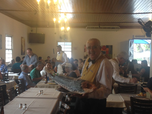 Waiter showing off an Amazon fish in the dining room before it is prepared by the chef